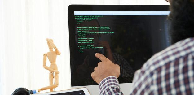 mão apontando para computador com codigo