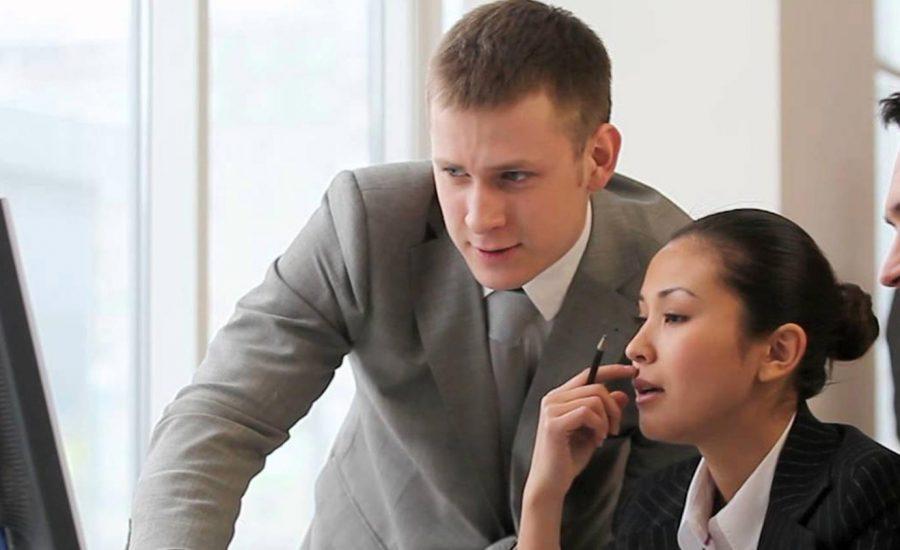dois homens executivos conversando com mulher executiva no computador
