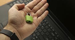 uma-mao-segurando-um-cadeado-verde-com-um-laptop-no-fundo-conceito-de-seguranca-cibernetica_181624-27999